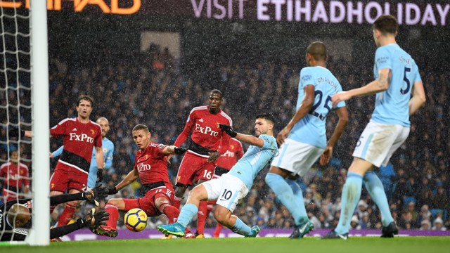 ON TARGET: Sergio Agüero slips the ball past Heurelho Gomes for City's third.