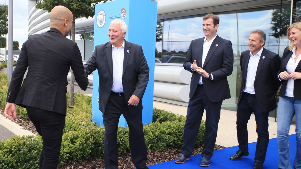 Mike Summerbee Ferran Soriano Txiki Begiristain and Vicky Kloss greet Pep Guardiola as he arrives at the City Football Academy for Cityzens Weekend